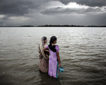 Women look out over the rising sea water. The sea in the Bay of Bengal is rising, affecting the hundreds of thousands of villagers living on the low islands in the south. Photo: Espen Rasmussen/PANOS