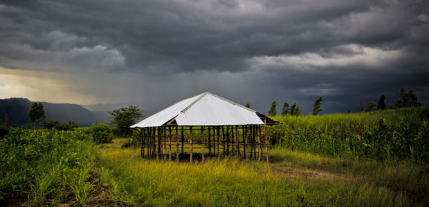 A church under construction sits on a verdant green field with dark grey storm clouds behind.