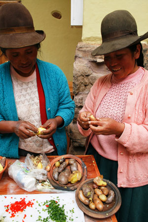 Two members of the Papamanka Cooperative, which runs a restaurant in the Potato Park, Cusco, Peru, prepare food.