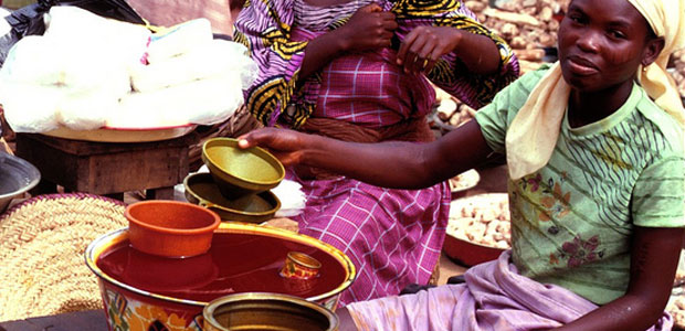 A woman sells palm oil in a market in west Africa.