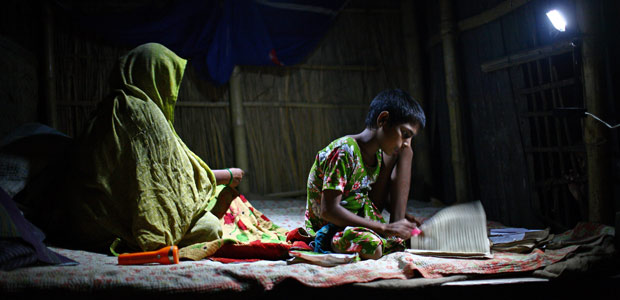 A girl studies under the light of a rechargeable solar lamp. Without the lamp she couldn't study at night as her home in Natore, Bangladesh has no access to electricity. Photo: G.M.B. Akash/PANOS