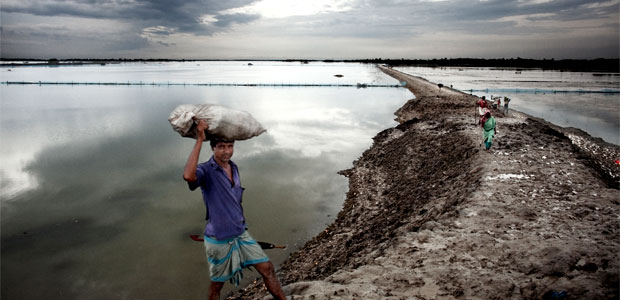 A man carries goods along a raised embankment