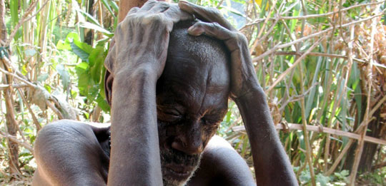 A Batwa man sits with his hands cupping his head.