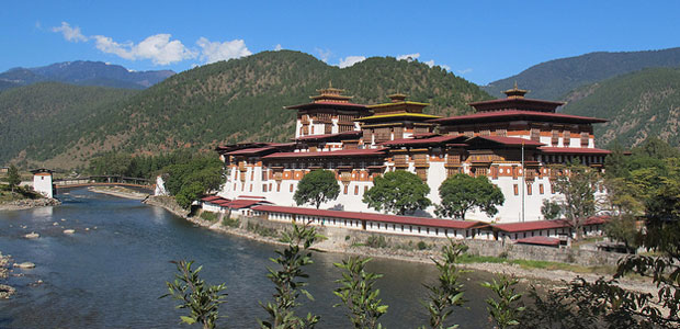 Picture of the Punakha Dzong, an administrative centre in Bhutan.A river runs past it in the foreground and wooded hills rise behind it.