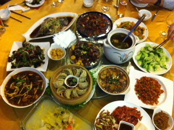 A table piled high with plates of dumplings and other Chinese foods. Food consumption in the country will continue to rise.