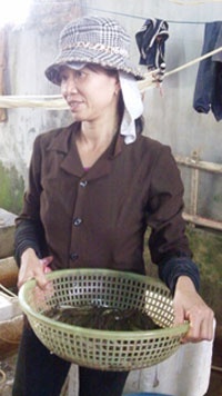 Woman holding a small basket containing fresh fish.