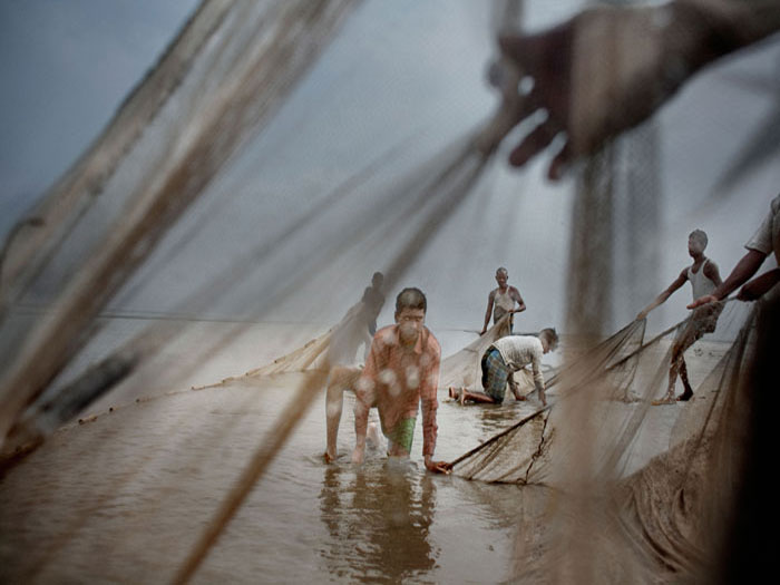 Boys fixing nets on beach