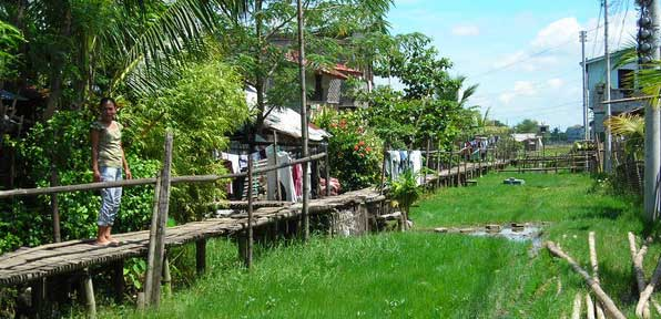 A woman walks along a bamboo walkway in Iloilo, Philippines.