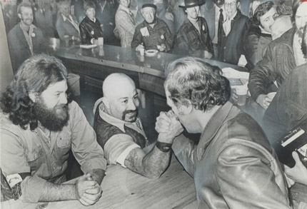 Canadian Prime Minister Pierre Trudeau arm-wrestles with a bartender at the Habitat conference