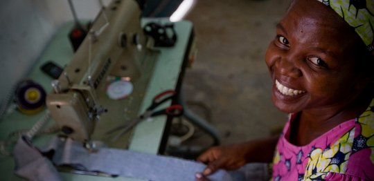 A smiling woman from Kenya sits beside her sewing machine.