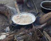 A pot with bubbling food sits cooking on an open fire.