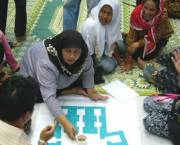 Women are gathered around a paper with squares on it talking.