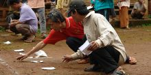 An image of crouching community members in a village in Champasak province, Laos identify areas where open defecation is taking place ahead of implementing sanitation measures (Photo: Viengsompasong Inthavong/World Bank, Creative Commons, via Flickr)