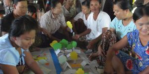 Women from near Rangoon, Myanmar are seated around a map with paper houses and trees talking and laughing.