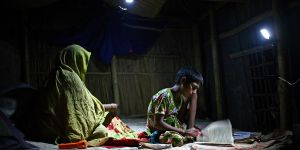 A girl studies under the light of a rechargeable solar lamp.