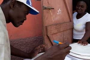 Two community leaders prepare service contracts for a novel container-based sanitation service before installing toilets in users' homes in Cap Haitien, Haiti (Photo: Felipe Jacome)