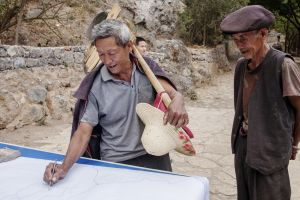 Indigenous mountain farmers examine a map of the Stone Village water management system, showing the water channels (Photo: Irene Song)