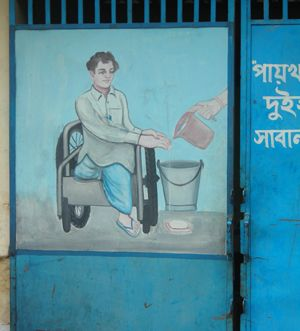 An image of the front of disabled toilet, featuring a picture of a person washing their hands, in a community sanitation facility in Kallyanpur, Dhaka (Photo: David Dodman/IIED)
