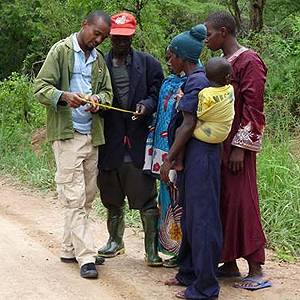 A representative from the Tanzanian CSO Mpingo Conservation and Development Initiative, talks with local community members about sustainable forest management practices (Photo: Maliasili Initiatives)