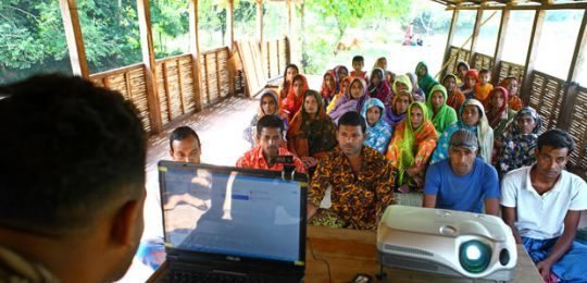 Group meeting on climate change on boat run by Shidhulai. Natore, Bangladesh. Photo: G.M.B. Akash/PANOS