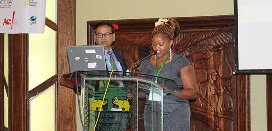 Standing alongside IIED senior fellow Saleemul Huq, Evah Wanjiru reads her poem 'Shadows in the child's memories' to participants at CBA9 (Photo: Matt Wright/IIED)