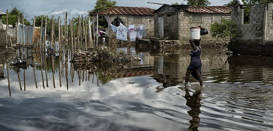 A women carries supplies through a flooded street in Cap-Haïtien, Haiti, after thousands were displaced following floods in 2014. Studies have shown that, when they are socially or economically disadvantaged, more women die in hurricanes and floods (Photo: United Nations Photo, Creative Comms via Flickr)