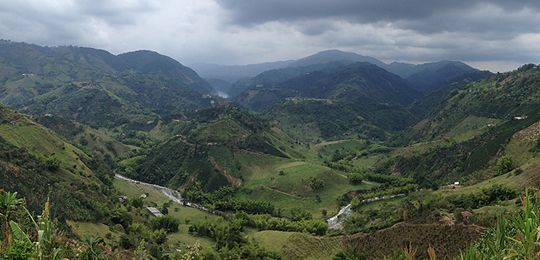 An image of a river splitting the hills of the Chinchiná River Basin in Colombia, one of eight countries in which IIED is working with the World Bank on natural capital accounting (Photo: Rosalind Goodrich/IIED)