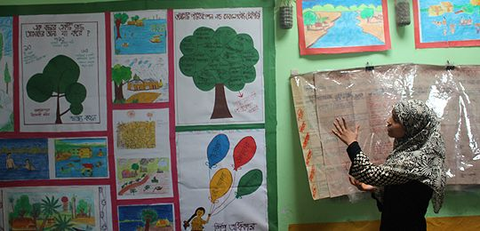 An image showing Salma, a member of a Eco-Friendly Child Club in Dhaka, pointing to paintings on the wall showing images of climate change. The children helped pressure authorities to clean a nearby canal (Photo: Matt Wright/IIED)