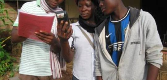 Youth and staff in Bamessing, Cameroon using a Garmin GPS unit to create a digital map of their community.