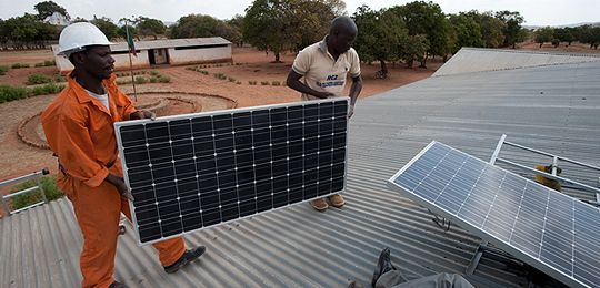 An image showing two men on the roof of a school in Zambia carrying out a macrosolar installation. Sustainable energy solutions for Least Developed Countries will be discussed at the event in London (Photo: Steve Woodward)