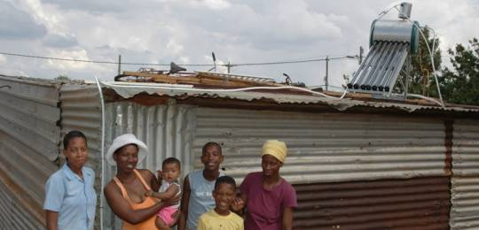 South Africa: Anna with friends and family in front of her new solar water heating system. It is often more cost-effective to provide energy services to poor communities via off-grid sources (Photo: Abri le Roux, Creative Commons via Flickr)