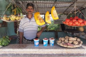An image showing a man behind a counter, displaying a variety of seasonal organic produce from a Cuban organopónico in Sancti Spiritus (Photo: Khanh Tran-Thanh/IIED)