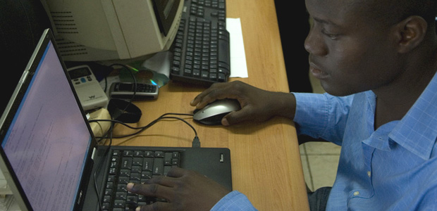 Picture of a man looking at a computer screen in the news studio of Joy FM studios in Accra.
