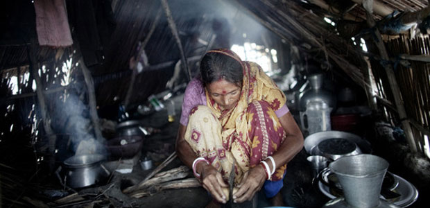 A woman prepares food in a small cabin built on a mud embankment surrounding Padma Pakur island in Bangladesh.