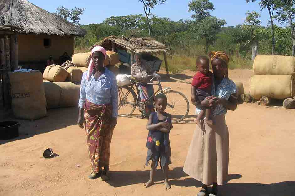 Family stands in front of bags of cotton awaiting collection