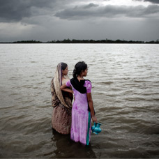 Women look out over flooded land