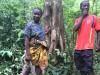 A man and a woman holding a machete stand in front of a tree in a forest
