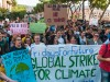 "Hundreds of protesting young people march behind a sign saying ""Global strike for climate change"""
