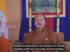 A seated man gives a speech to a camera directly in front of him, next to the Bhutan national flag