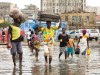 People wading through the flood waters and carrying their belongings