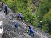 Miners on a steep hillside mine tungsten