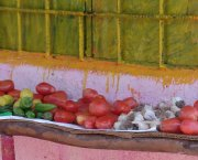 Tomatoes and other vegetables on a shelf outside a house