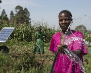 Woman looking to the front holding a water hose, a solar panel in the background