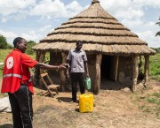 Man stands next to a hut and a jerrycan. Another man, wearing red, points to the right.