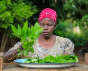 Woman puts greens on a plate