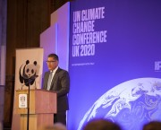 "Man speaking in front of a wall that reads ""UN Climate Change Conference UK 2020"""