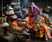 Woman cooks using wood fire