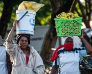 Two women carry buckets with fruits on their heads.