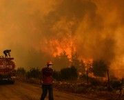 A wildfire burns a forest. A man climbs a fire engine and another one, wearing a mask, walk on the road.