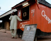 A man on the phone outside a small orange hut. A nearby sign advertises prices for mobile phone air-time.